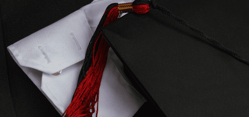 A graduation cap with a red tassel laying on top of a white shirt sleeve.