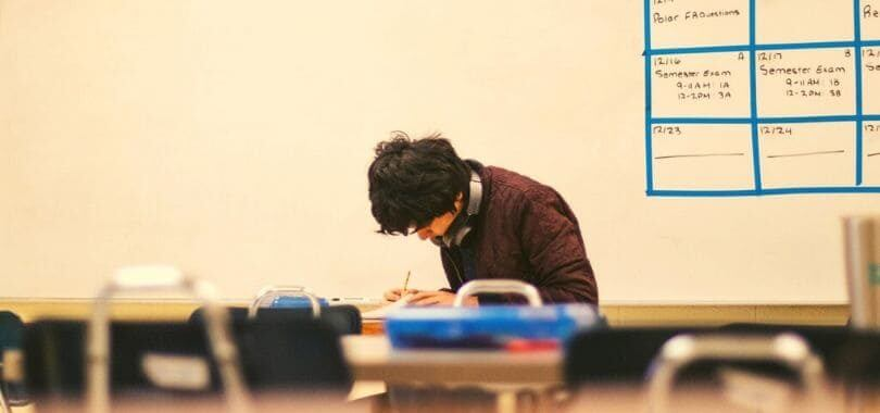 A high school student sitting in a classroom working on an assignment.