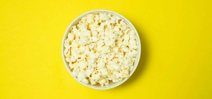 A bowl of popcorn against a yellow background.