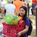 Student carrying her dorm supplies in a pink basket while moving into college.