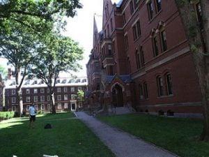Student standing outside Harvard University red brick building.