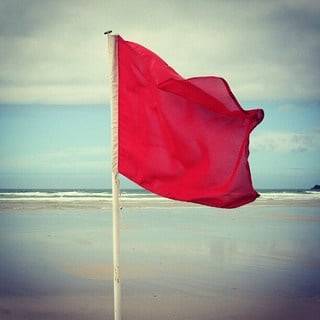 A red flag on the sea side.