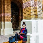 Female college student leaning on a building post while studying.