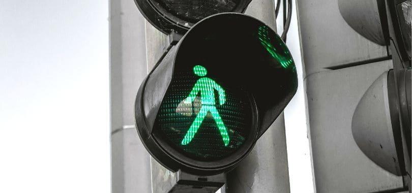 A crossing light showing a green man walking.