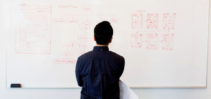 A student standing in front of a whiteboard with their back facing the camera.