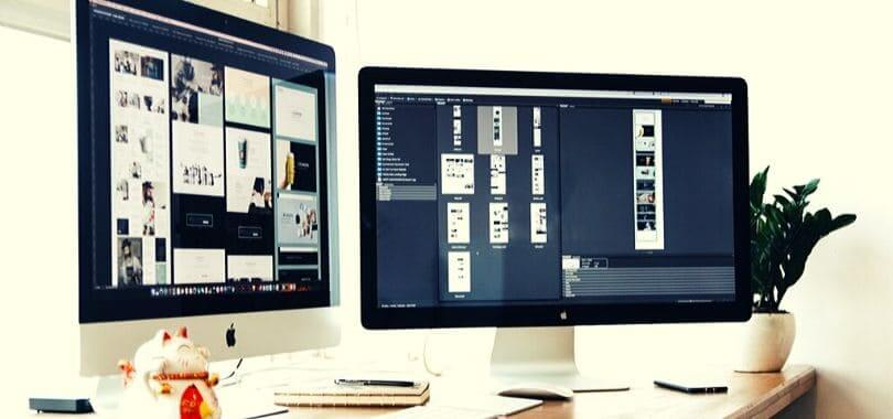 Two computer monitors on a white desk.