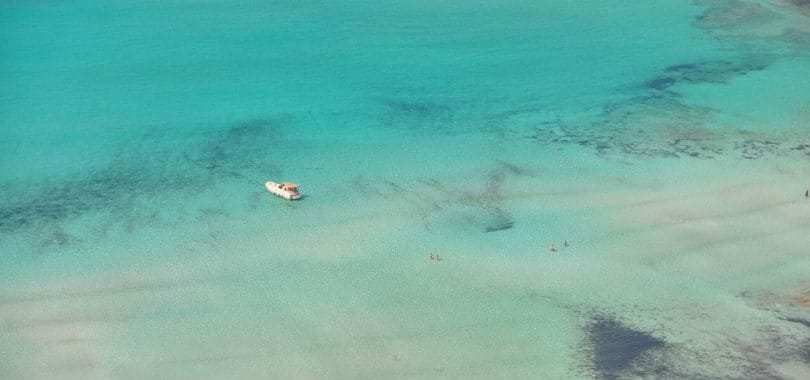 A overhead shot of the sea with a small white ship floating in it.