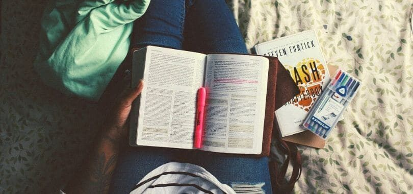 A student with a book and a pink highlighter in their lap