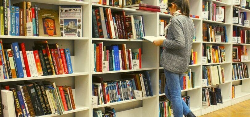 A college student standing in front of multiple bookshelves reading a book.