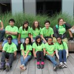 Twelve students posing for a picture, all wearing a green shirt.