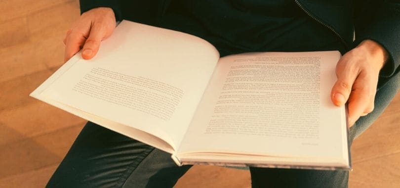 A student holding an open textbook in their lap.