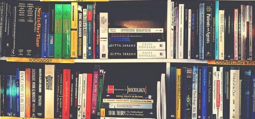 Rows of sociology books on bookshelves.