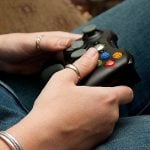A student's hand holding a game controller.
