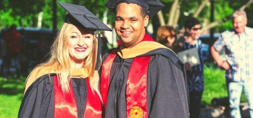 Two students graduating, wearing black graduation robes.