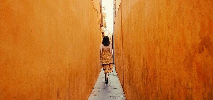 A person walking down a narrow alleyway.
