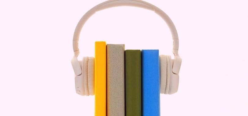 Four books held together with a pair of headphones.