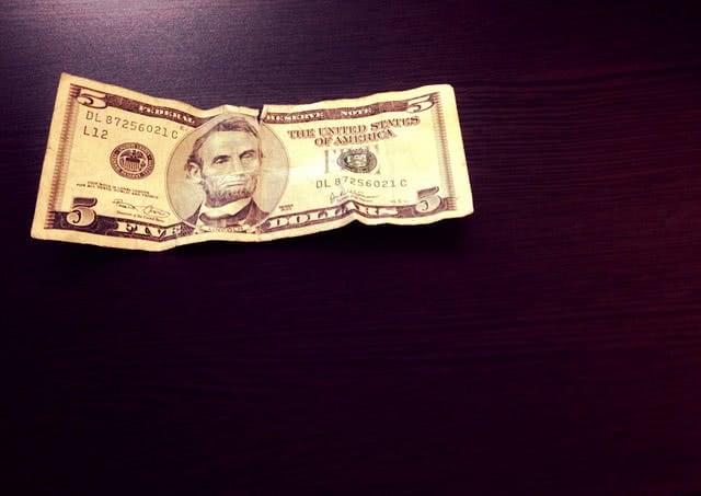 Five dollar bill slightly cramped.