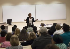 A professor talking to students and parents in a classroom.