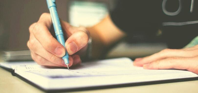 A person holding a blue pencil writing in a notebook.