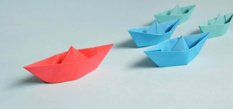 Pink, blue and green origami boats.