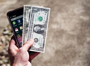 Hand holding a phone and money.
