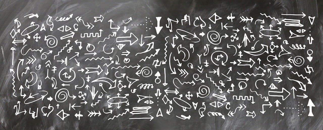 Multiple arrows drawn on a blackboard.