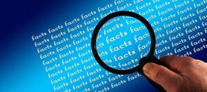 """A hand is holding a magnifying glass over a bunch of text that says """"facts."""""""