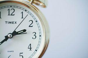 Half of a rose-gold Timex classic alarm clock.
