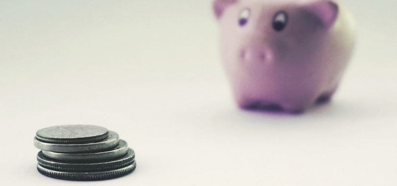 A few coins stacked together with a piggy bank in the background.