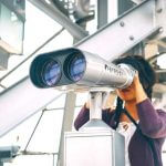 A student looking through a pair of binoculars.