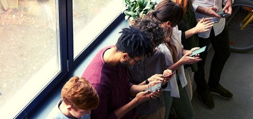 Students leaning against a window ledge on their phones.