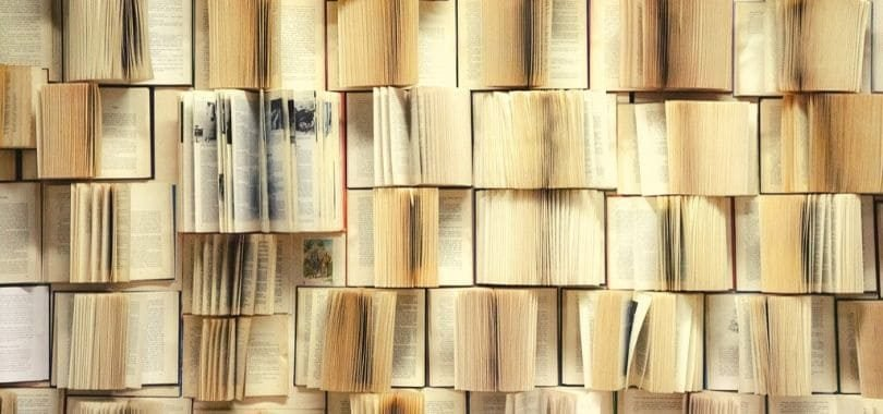 Rows of books opened towards the camera, with one large textbook standing out.
