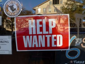 """""""Help Wanted"""" signage behind a glass wall."""