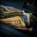 An open black wallet with money inside.
