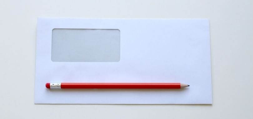 An empty white envelope with a red pencil sitting on top of it.