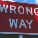 """A red sign with white lettering that says """"wrong way."""""""