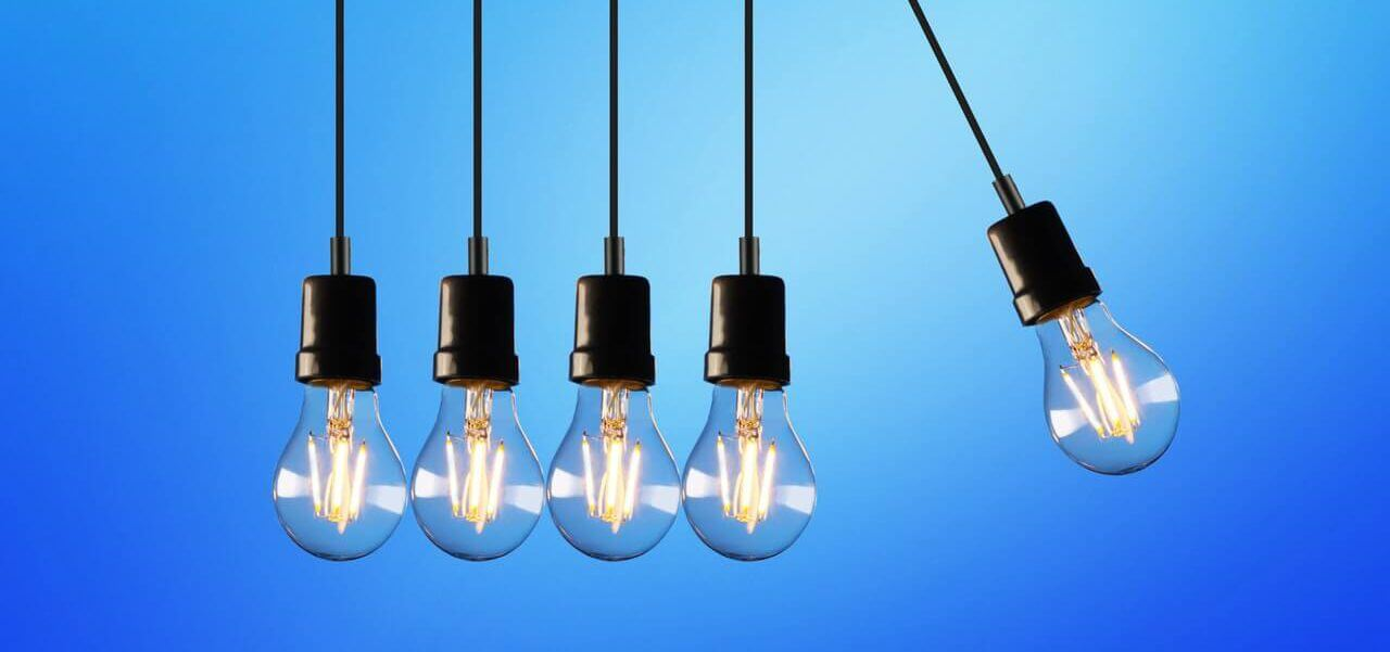Five light bulbs with the right-most light bulb swinging.