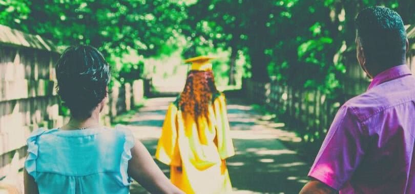 Two parents hold hands while watching their daughter graduate and walk down a road.