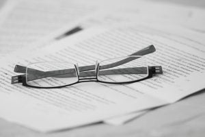 Eyeglass is on the top of white papers.