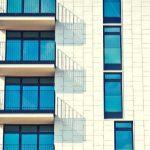 A white brick apartment building against a blue sky.