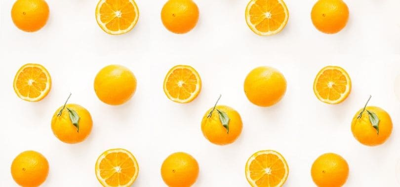 Whole and halved oranges in rows.
