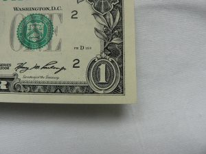 One dollar bill showing only the lower right corner.