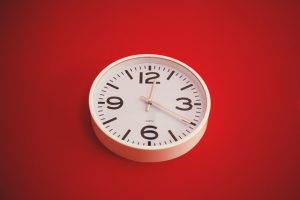 White wall clock against red background.
