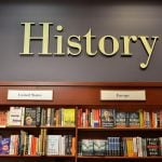 """Bookshelf and a word """"History"""" above it."""