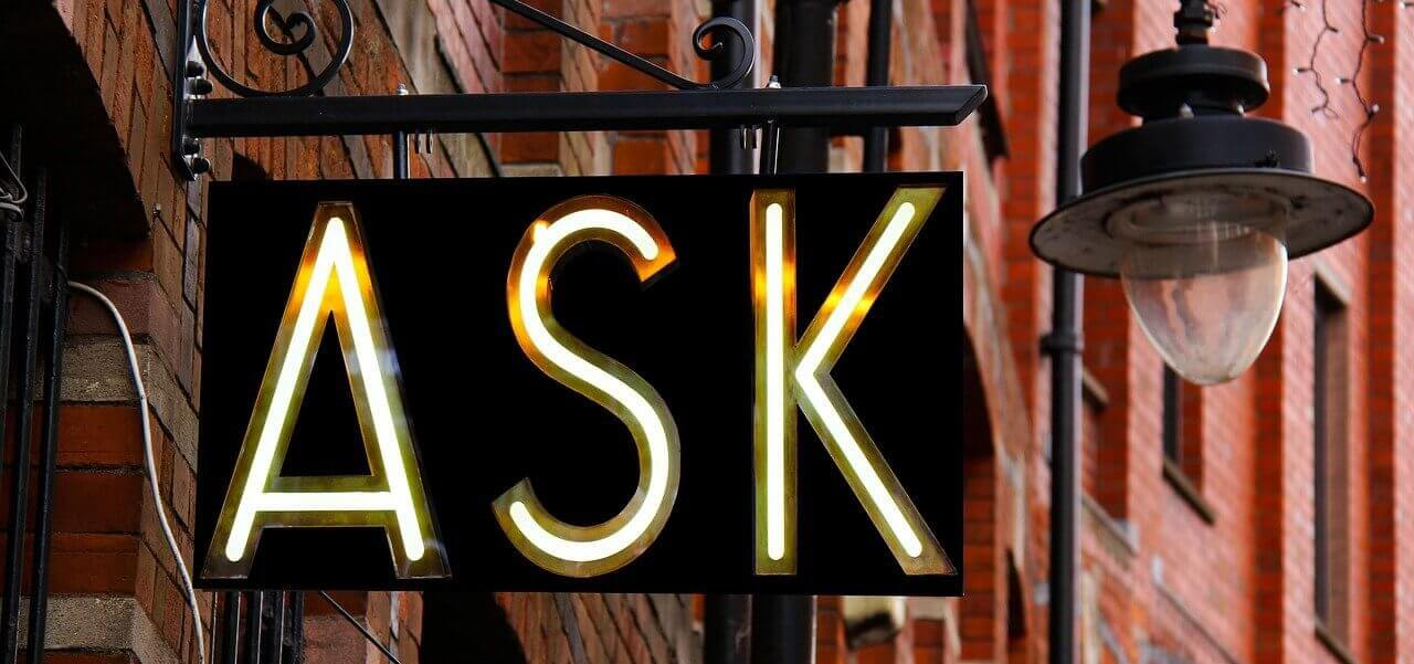 """A sign that says """"ask"""" with a light fixture next to it."""