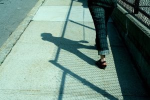 A student walking down the sidewalk with a visible shadow, shown from the waist down.
