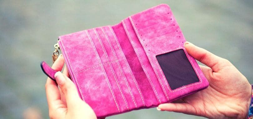 A person holding an empty pink wallet.