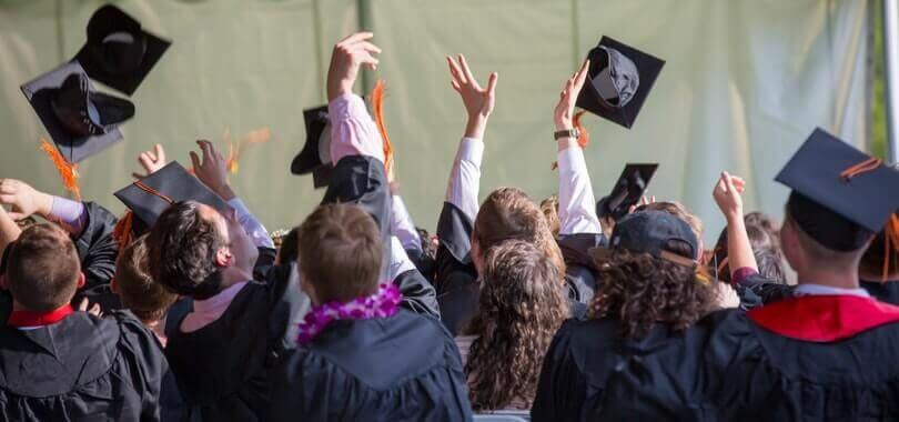 Graduating college students tossing their caps into the air.