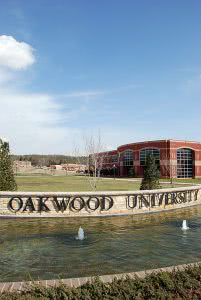 Oakwood University's name in brass lettering with the school building in the background.