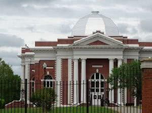 Tuskegee University campus building behind a black gate.